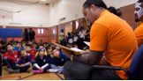 "First- and second-graders from Johnson Elementary School listen as The Usos read ""Not Your Typical Dragon."""
