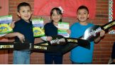 "After meeting The Usos, the students show off their ""Reading Superstar"" titles."
