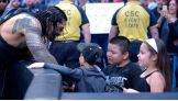 WWE World Heavyweight Champion Roman Reigns greets his new friend Ivan at ringside before Raw's main event.