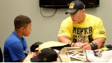 John Cena talks to Fabian while signing autographs for the young WWE fan.