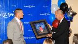 David Williams, President and Chief Executive Officer for the Make-A-Wish Foundation of America, presents an award to Cena.