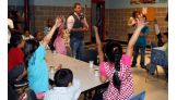 The WWE NXT host asks the children questions about what they've learned.