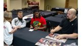 The Superstars sign this year's WrestleMania Reading Challenge poster.