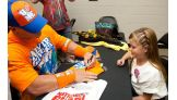 Cena signs an autograph for Crystal Courvelle.