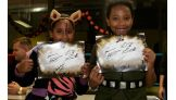 Two costumed girls show off their Hart Dynasty autographs.