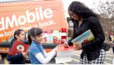 At the end of the event, they sign autographs for the students near the We Give Books ReadMobile.