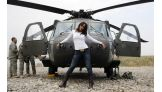 Layla stands in front of a helicopter in Iraq